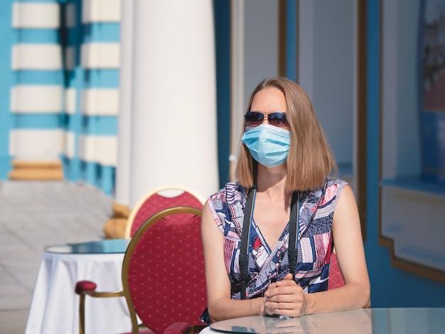 Una turista femminile con una maschera medica è seduta al tavolino di un bar sulla strada. sicurezza in un luogo pubblico durante l'epidemia di covid-19.