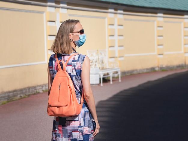Turista femminile in una mascherina medica con uno zaino sulla strada. sicurezza in un luogo pubblico durante l'epidemia di covid-19.