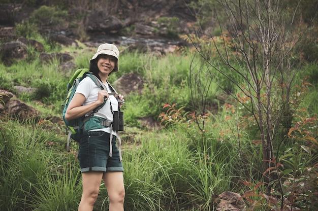 Turista femminile che cammina nel bosco con zaino e binocolo. il camper della ragazza esplora nella foresta.