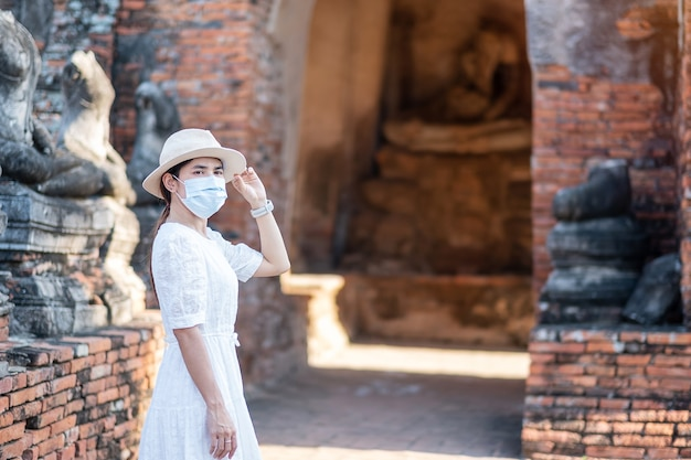 Turista femminile che indossa la mascherina chirurgica che visita il tempio di wat chaiwatthanaram