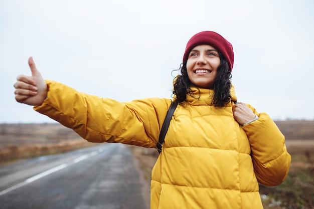 Turista femminile con uno zaino che indossa giacca gialla e cappello rosso cattura un'auto sulla strada.