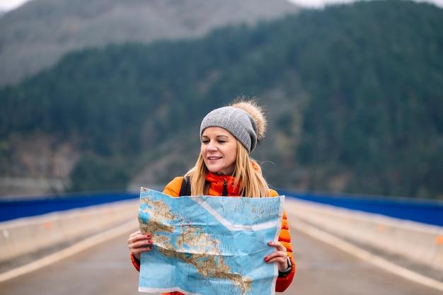 Turista femminile con una mappa che cammina su una strada con un paesaggio di montagna verde