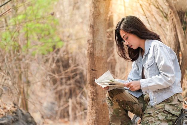 Turiste che guardano mappe, programmi di trekking verso la loro destinazione