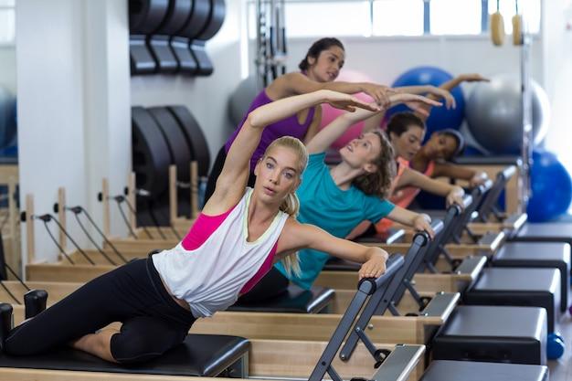 Allenatore femminile che assiste un gruppo di donne con esercizi di stretching sul riformatore