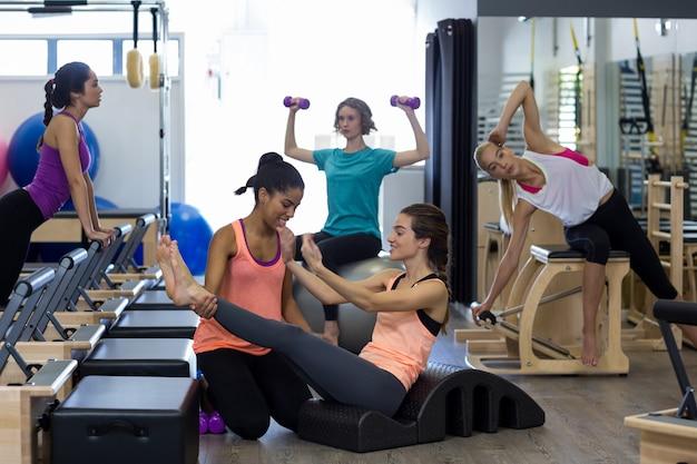 Allenatore femminile che assiste la donna con esercizio di stretching sulla canna dell'arco