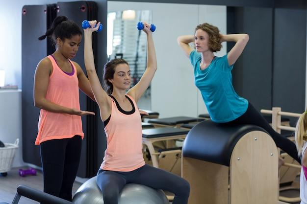 Allenatore femminile che assiste la donna con esercizio di stretching sulla palla fitness