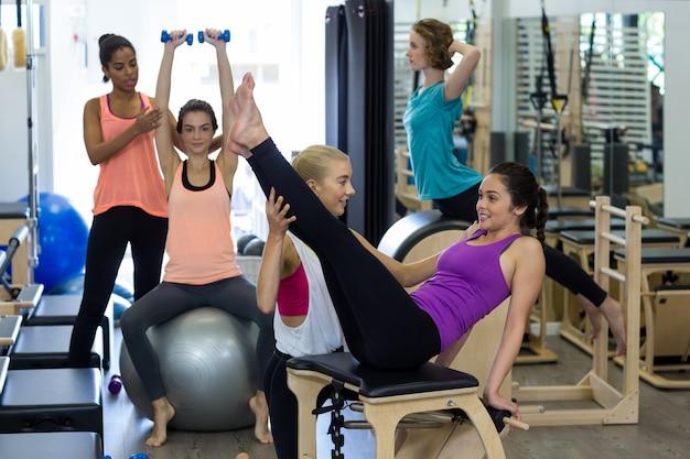 Allenatore femminile che assiste la donna con esercizio di stretching sul riformatore