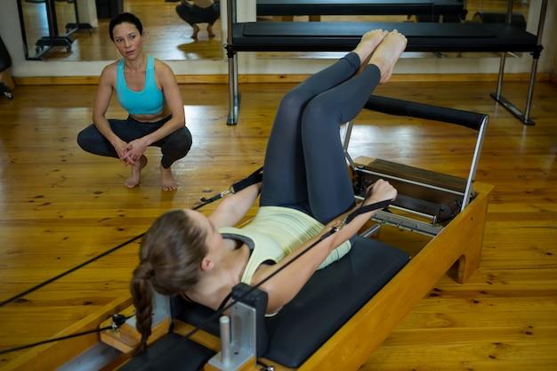 Allenatore femminile che assiste la donna con esercizio di stretching