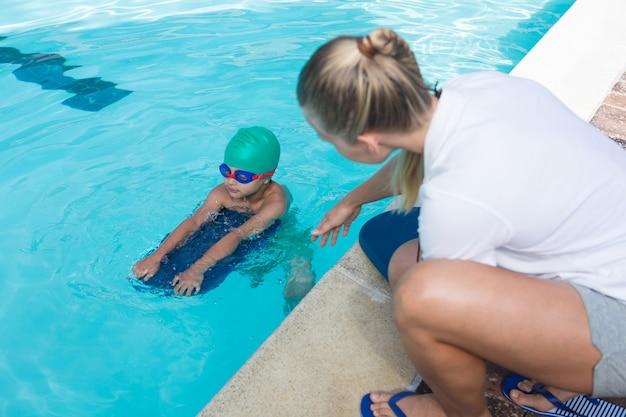 Allenatore femminile che prepara un ragazzo per nuotare