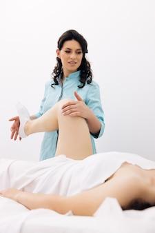 La donna allena la forza muscolare con un medico professionista in una moderna clinica di riabilitazione