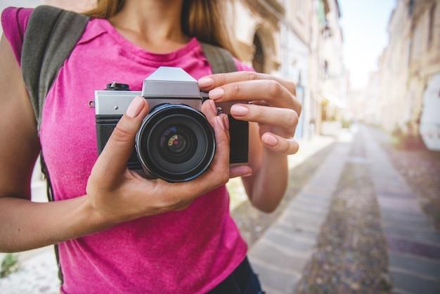 Blogger di viaggio femminile con fotocamera retrò