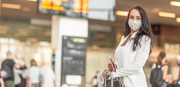 Viaggiatrice in tempi di covid in possesso di carta d'imbarco e passaporto in attesa nella hall dell'aeroporto.