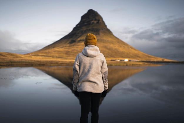 Viaggiatore femminile alla montagna di kirkjufell, islanda