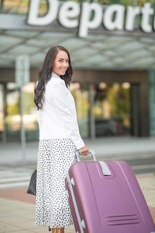 Viaggiatore femminile che tira un grosso bagaglio poco prima di entrare nella sala partenze dell'aeroporto.