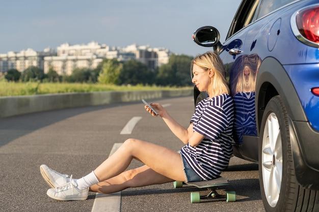 La viaggiatrice legge e sfoglia il messaggio nello smartphone seduto in macchina su skateboard in strada con il tramonto