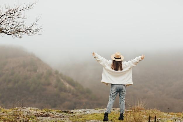 Una viaggiatrice in piedi sulla montagna e guardando una bellissima montagna e un mare di nebbia.