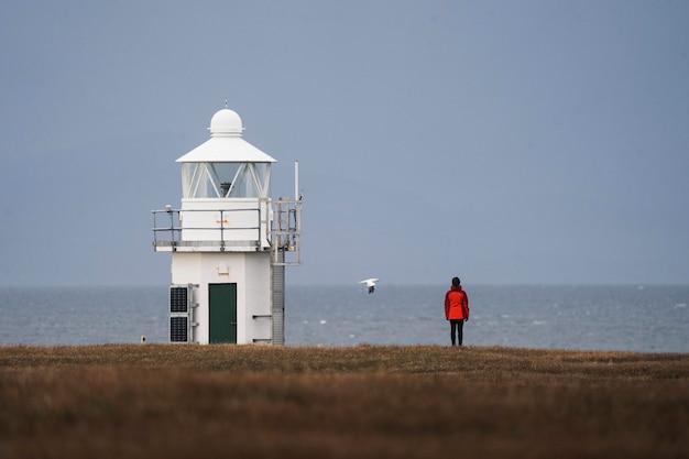 Viaggiatore femminile al faro di vaternish sull'isola di skye, scotland