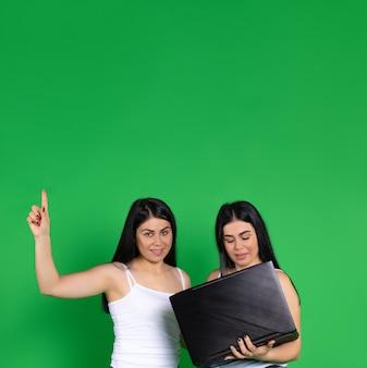 Gemelli femminili su una che tiene un computer portatile, punta il dito verso l'alto