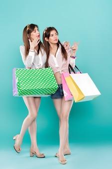 Gemelle con borse della spesa su sfondo blu
