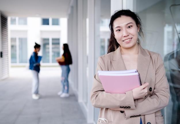 Studente universitario femminile che tiene le cartelle