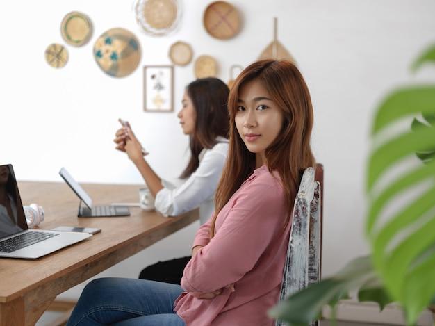 Studente universitario femminile che si siede sulla sedia al tavolo in caffè con il suo amico e dispositivi digitali