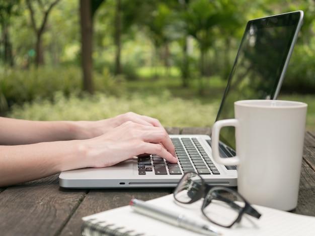 Uso femminile su computer portatile con tazza di caffè bianco sulla vecchia scrivania in legno in giardino.