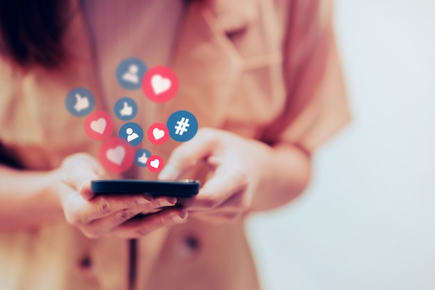 Donna che utilizza smartphone con i social media
