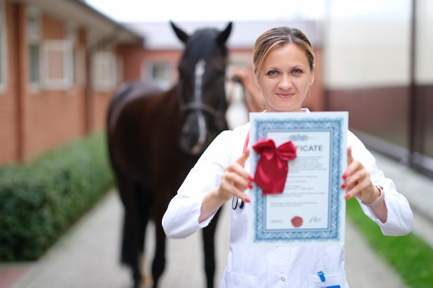 Veterinario femminile in possesso di certificato medico per cavallo