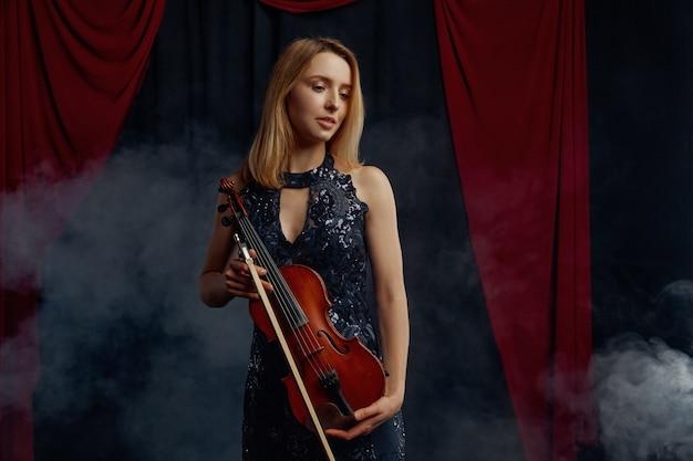 Il violonista femminile tiene arco e violino in stile retrò. donna con strumento musicale a corde, arte musicale, musicista gioca sulla viola