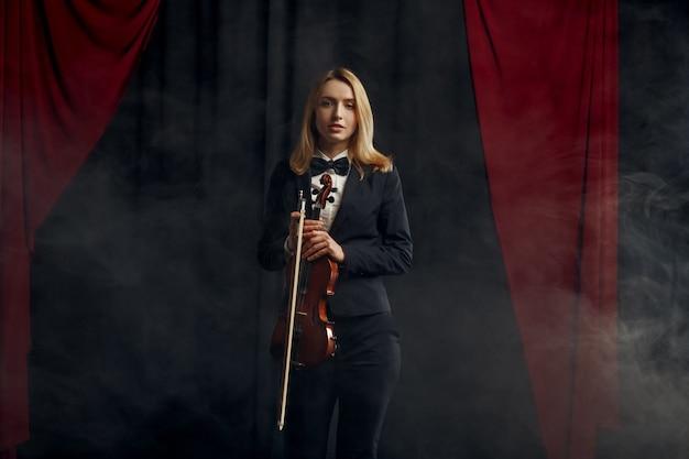Il violonista femminile tiene il violino in stile retrò. donna con strumento musicale a corde, arte musicale, musicista gioca sulla viola