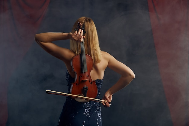 Violinista femminile con arco e violino dietro la schiena, performance virtuosa sul palco. donna con strumento musicale a corde, arte musicale, musicista gioca sulla viola