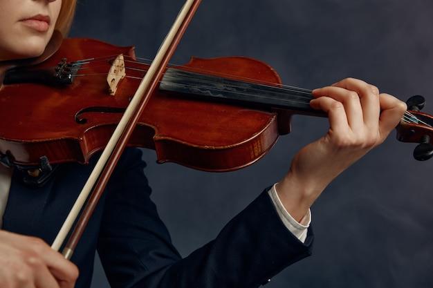 Violinista femminile con arco e violino, performance sul palco. donna con strumento musicale a corde, arte musicale, musicista gioca sulla viola