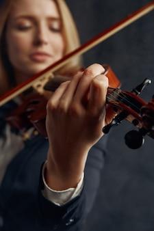 Violinista femminile con arco e violino, concerto solista sul palco. donna con strumento musicale a corde, arte musicale, musicista gioca sulla viola