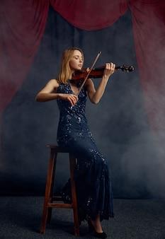 Violinista femminile con arco e violino, concerto solista sul palco. donna con strumento musicale a corde, musicista gioca sulla viola