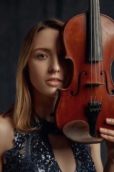 Violinista femminile con violino retrò in faccia. donna con strumento musicale a corde, arte musicale, musicista gioca sulla viola