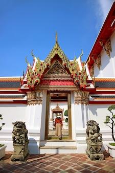 Visitatore femminile che entra nella splendida entrata del tempio di wat pho a bangkok