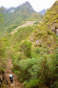 Visitatrice che scatta foto della cittadella di machu picchu dal pendio del monte huayna picchu peru