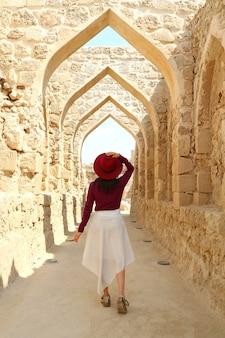 Visitatrice che cammina lungo gli iconici archi dell'antica fortezza del bahrain a manama, bahrain