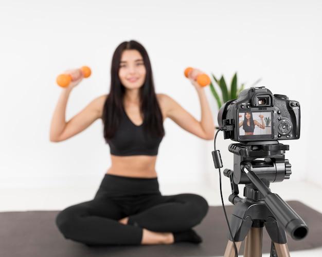Vlogger femminile a casa con la macchina fotografica che si esercita usando i pesi