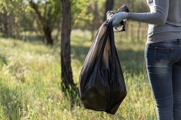 Una volontaria raccoglie la spazzatura nella foresta. concetto di inquinamento ambientale.