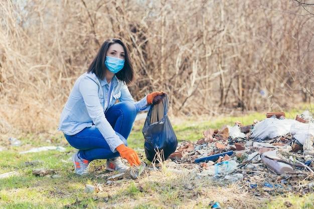 Il volontario femminile tiene una borsa con plastica raccolta che pulisce la foresta e il parco dalla spazzatura