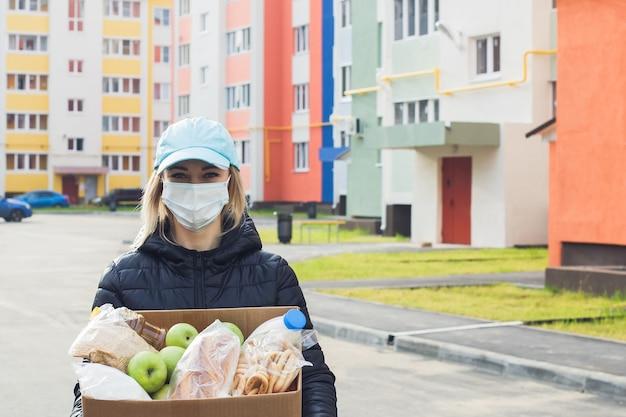 Una volontaria che indossa una maschera protettiva cammina per strada con una scatola di generi alimentari e donazioni.