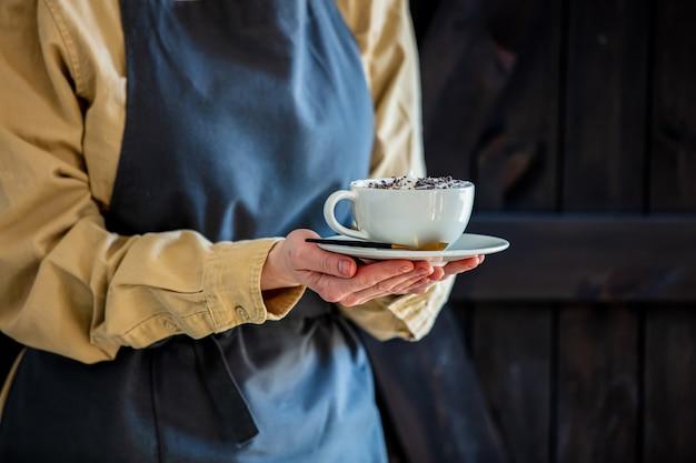Il cameriere femminile in un grembiule tiene un cappuccino