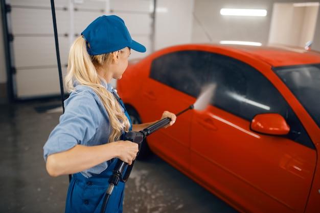 La rondella femminile in uniforme pulisce l'auto con la pistola ad alta pressione nelle mani