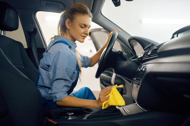 Rondella femmina con spugna pulisce il rivestimento della portiera dell'auto, servizio di autolavaggio. la donna lava il veicolo, la stazione di autolavaggio, l'attività di autolavaggio