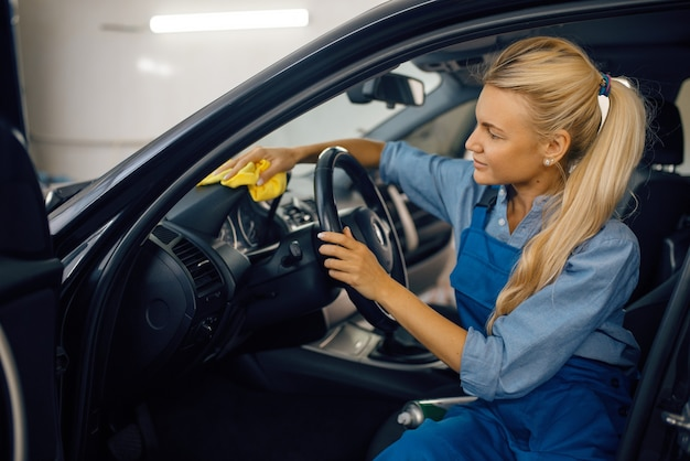 Rondella femmina con spugna pulisce l'interno dell'automobile, servizio di autolavaggio. la donna lava il veicolo, la stazione di autolavaggio, l'attività di autolavaggio