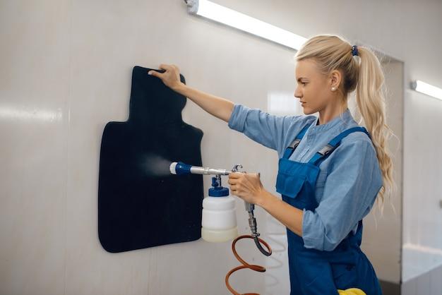 Rondella femmina con pulitore a vapore pulisce i tappetini delle automobili, il servizio di autolavaggio. la donna lava il veicolo, la stazione di autolavaggio, l'attività di autolavaggio