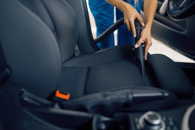 La rondella femminile con l'aspirapolvere pulisce l'interno dell'automobile, il servizio di autolavaggio. la donna lava il veicolo, la stazione di autolavaggio, l'attività di autolavaggio