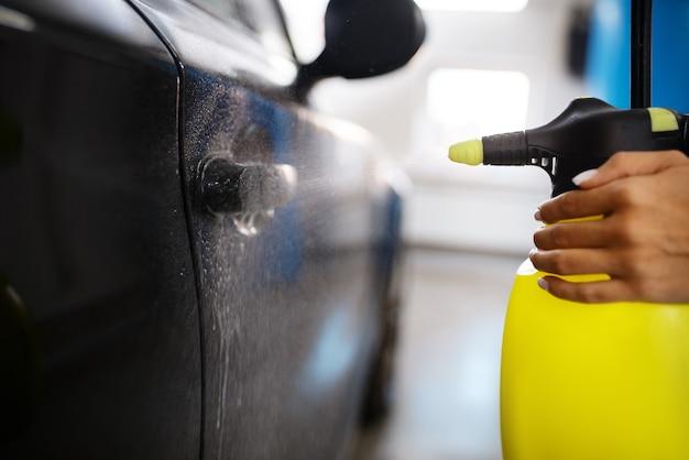 Rondella femmina con cera spray pulisce automobile, ceretta sul servizio di autolavaggio. la donna lava il veicolo, la stazione di autolavaggio, l'attività di autolavaggio