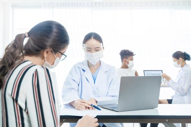 La donna indossa la maschera facciale contro il covid19 sullo sfondo con gli infermieri che usano la siringa per iniettare il vaccino